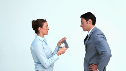 Woman putting adhesive tape on a businessman's mouth