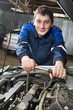 happy automotive mechanic at work with wrench