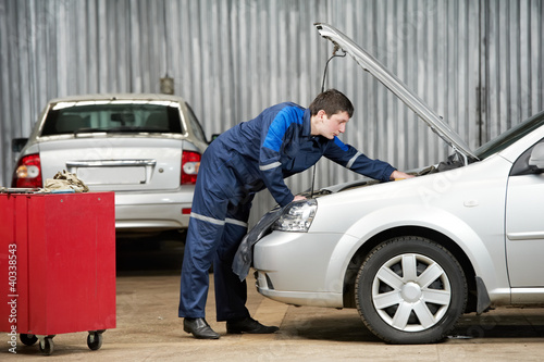 car mechanic diagnosing auto engine problem