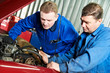 two car mechanic diagnosing auto engine problem