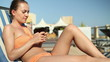 Young woman using cellphone while lying on sunbed
