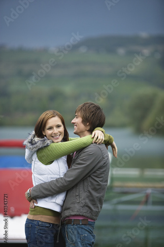 Young couple embracing, smiling