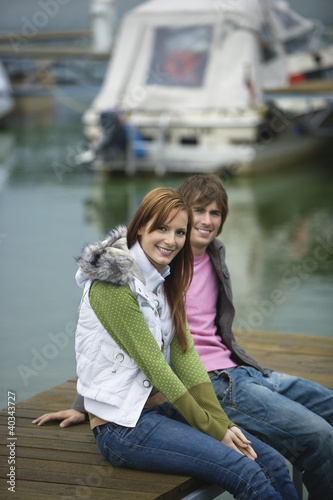 Young couple sitting on jetty, smiling, portrait