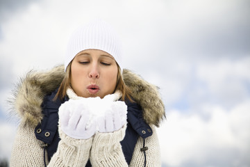 Mid adult woman blowing snow held in cupped hands