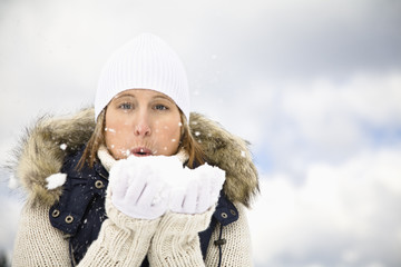 Mid adult woman blowing snow held in cupped hands, portrait