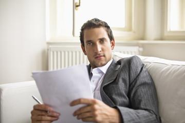 Businessman holding pen and document, portrait