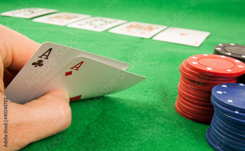 A pair of aces in a hand with chips and cards in the background
