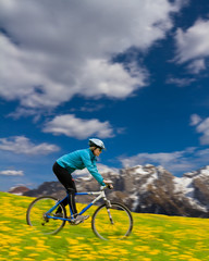 Spring bike riding - woman downhill on bike in dandelion