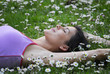 Joven mujer recostada sobre flores en primavera.