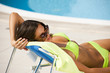 Woman lying on deckchair by swimming-pool