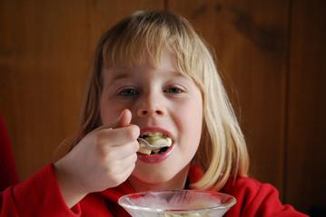 Pequeña niña feliz comiendo.