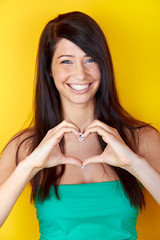 smiling beautiful girl showing a heart with hands