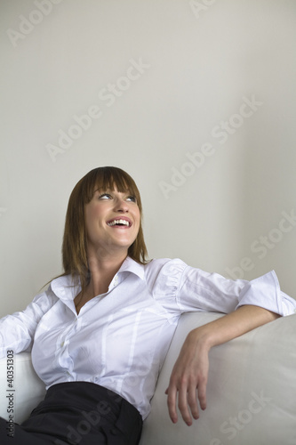 Mid adult woman sitting on sofa, smiling, looking up