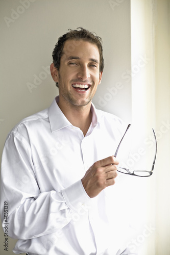 Mid adult man holding glasses, portrait