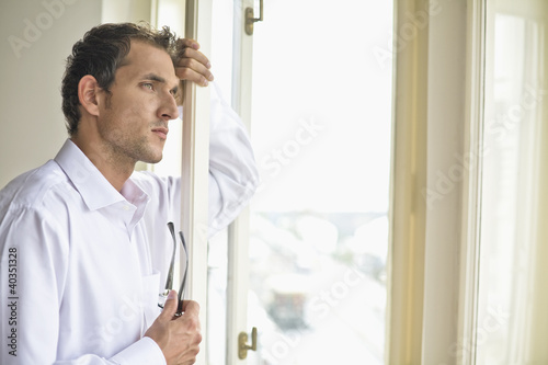 Mid adult man leaning against window, holding glasses