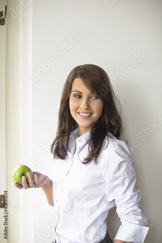 Young woman holding green apple in hand