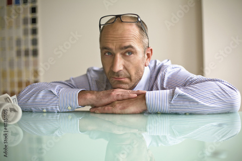 Businessman leaning on table, close-up