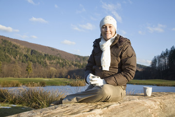 Mid adult woman sitting on wooden log, smiling
