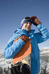 Young man holding snowboard, smiling