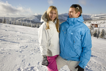 Young couple standing on snow, smiling