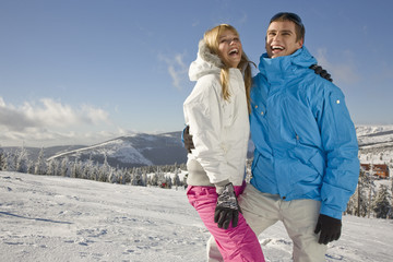 Young couple standing on snow with arms around, smiling