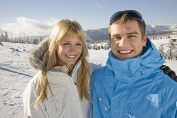 Young couple standing on snow, smiling, portrait
