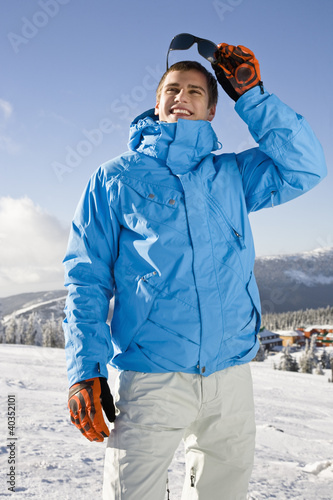 Young man standing on snow, smiling