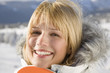 Young woman holding snowboard, smiling, portrait