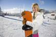 Young woman holding snowboard, smiling