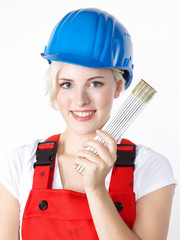 Young woman with building-site helmet and yardstick