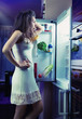 Woman wearing pajamas looking at fridge