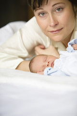 Mother with baby on bed