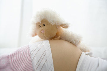 Pregnant woman lying with teddy bear on belly, midsection