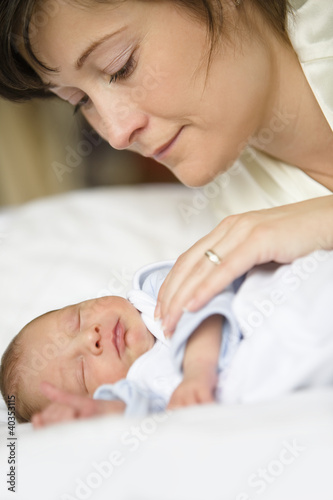 Mother with baby on bed, close-up