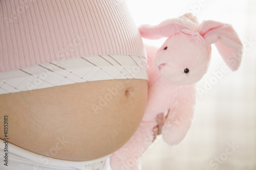 Pregnant woman holding stuffed toy, midsection, close-up