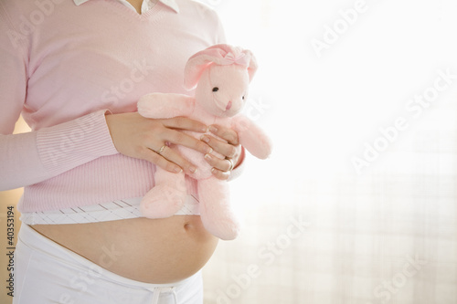 Pregnant woman holding stuffed toy, midsection, side view
