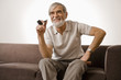 Senior man holding smoke pipe, smiling