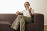 Senior man sitting on sofa with legs crossed at knee