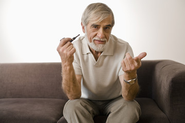 Senior man holding smoke pipe, portrait