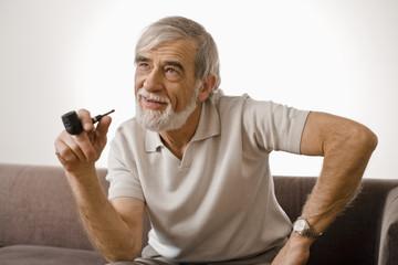 Senior man holding smoke pipe, smiling