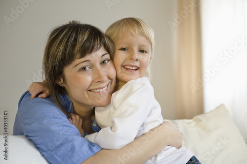 Mother embracing daughter, smiling, portrait