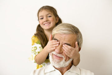 Girl covering senior man's eyes, smiling