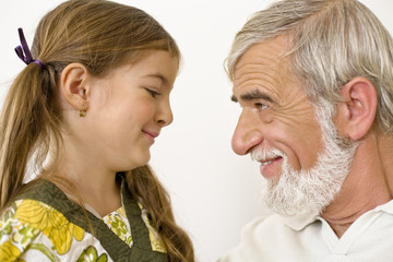 Senior man with granddaughter, smiling, close-up