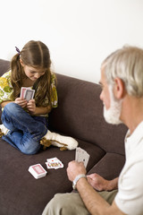 Girl playing cards with grandfather