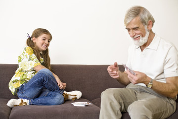 Girl playing cards with grandfather, smiling