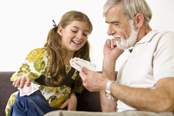 Senior man and girl looking at playing cards