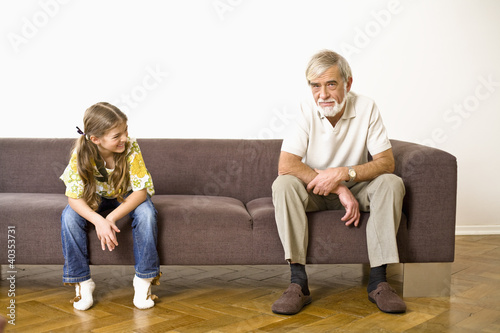 Girl looking at grandfather, smiling