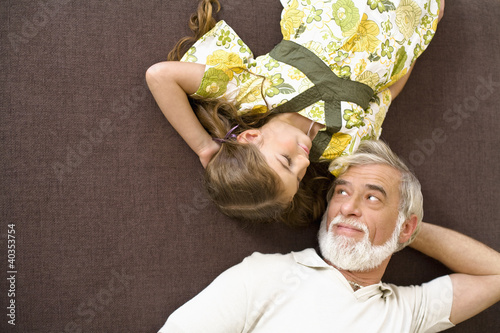 Senior man and girl resting on sofa