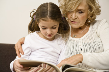 Senior woman with granddaughter looking at photograph album