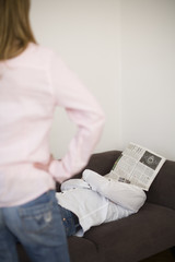 Woman standing while man sleeping with newspaper on face